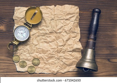 Compass, train bell, money and blank crumpled brown page paper on wooden table. Adventure, treasure hunt, journey or travel concept.