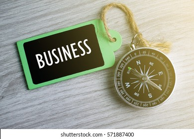 Compass and wooden tag written with BUSINESS on grey background.
