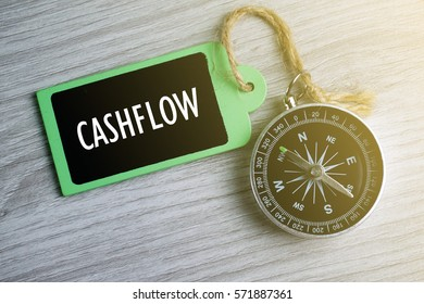 Compass and wooden tag written with CASH FLOW on grey background.