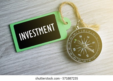 Compass and wooden tag written with INVESTMENT on grey background.