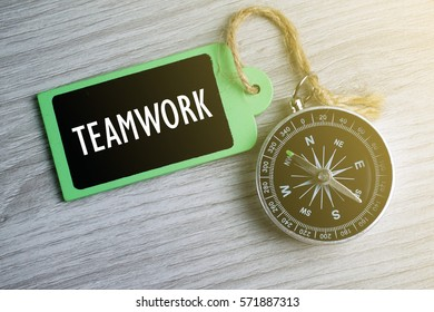 Compass and wooden tag written with TEAMWORK on grey background.