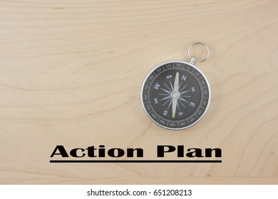 compass with word action plan isolated on wooden background