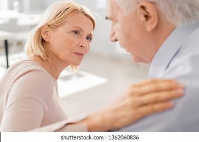 Compassionate aged blonde female looking at suffering senior man while keeping her hand on his shoulder