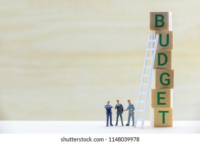 Compayny annual budget control, microeconomics concept : Miniature figurine top management team e.g CEO, CFO discuss and make decision on budget that include planned sales volumes and revenues, costs