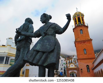 Competa, Spain - September 29, 2018: Bronze statue of two dancers in old market square against tall clock tower