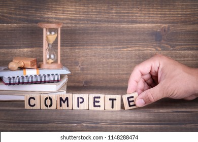 compete. wooden letters on the office desk, informative and communication background