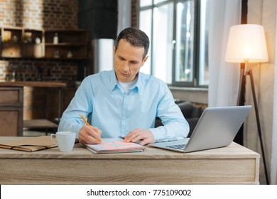 Competent businessman. Attentive brunette man bowing head and leaning elbows on table while sitting at his workplace
