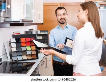 Competent positive seller consulting female customer in store of kitchen furnishing and appliances