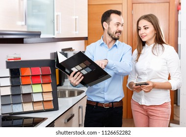 Competent smiling cheerful seller consulting female customer in store of kitchen furnishing and appliances
