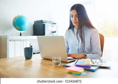 Competent young business secretary working at a laptop at a wooden desk surrounded by colorful memo notes to organise and prioritise her tasks