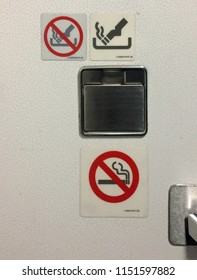 "Competing placards send mixed messages in an airplane lavatory: ""not an ashtray"" ""yes an ashtray"" and ""no smoking"""