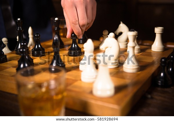 Competition between companies, enterprises, firms. Closeup of chess pieces on chessboard. Rich men playing chess in restaurant. Business concept.
