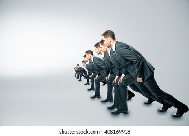 Competition concept with businessmen about to run on grey background
