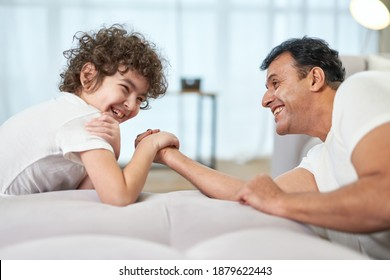 Competition. Cute latin boy and his father having fun together at home while armwrestling lying on the couch