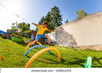 Wettbewerbsfähiges aktives Spiel - Junge springt über Hindernisse
