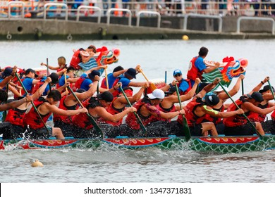 A competitive boat racing tournament in the traditional Dragon Boat Festival in Taipei, Taiwan, with vigorous athletes pulling powerfully on their oars & competing strenuously in three colorful boats