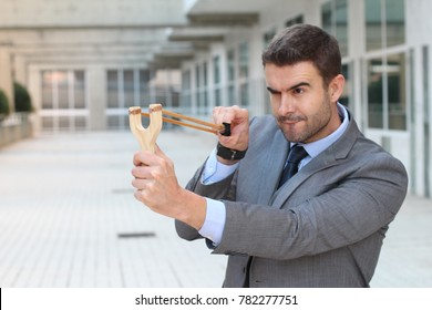 Competitive businessman aiming with a slingshot