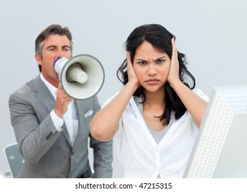 Competitive businessman shouting through a megaphone  in the office
