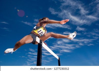 Competitive female athlete jumping hurdle in race on running track