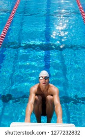 Competitive male swimmer on starting block ready for race start