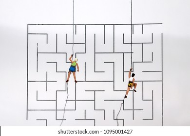 Two miniature climbers climbing through a rope on the maze. A competitive society concept.