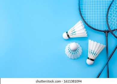 Competitive sports and high performance in tournament match conceptual idea with badminton rackets and shuttlecock (birdie) isolated on blue court background with copy space