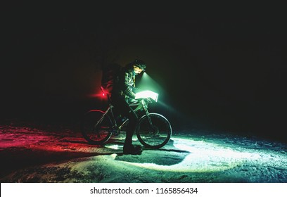 Competitor of winter night mtb race stop for possition control. Biker with white fat bike looking into map in night while snowing.