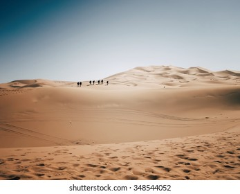 Competitors in the Marathon des Sables traverse a sahara desert dune