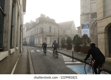 Compiegne, France - April 10, 2016: Bicycle commuters riding through ancient European city on moody, foggy morning