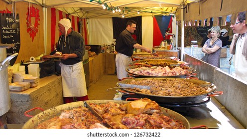 COMPIEGNE, FRANCE - MAY 22: Unidentified men cook and sell various meat snacks in a stall on a medieval market held during annual Joan of Arc festival on May 22, 2010 in Compiegne, France.
