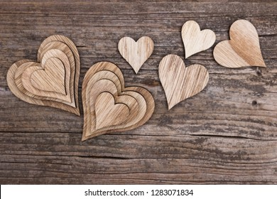 Compilation of many different wooden hearts on a wooden background