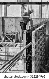 Compilation of metal structures for pouring concrete. Preparations for the inundation of supporting walls. The metal frame and the reinforcing mesh. Working fasten metal plate on a construction site.