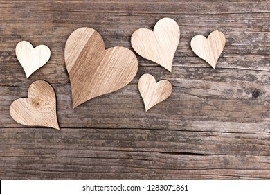 Compilation of several wooden hearts on wooden background