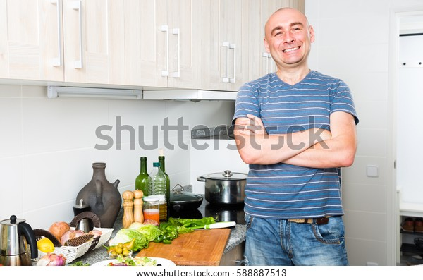 complacent ordinary positive guy stands proudly in kitchen hands clasped