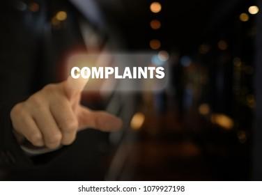Complaints concept. Businessman pointing the text Complaints button on virtual screens.