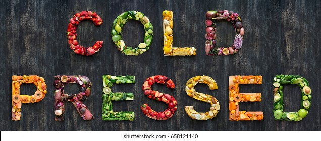 complete collection of alphabet letters made from healthy green fruit and vegetables on rustic distressed texture, overhead flat lay