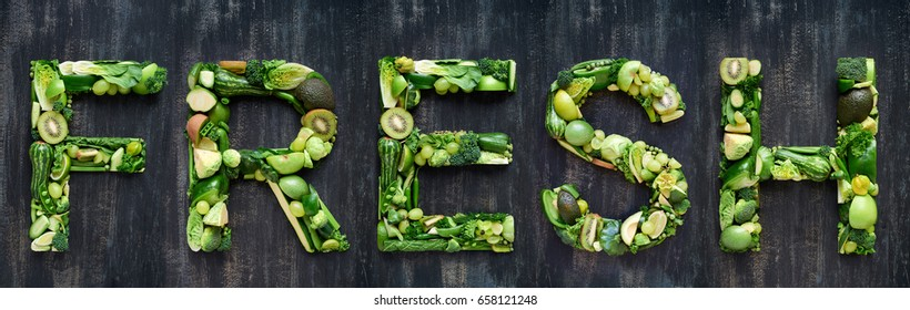 complete collection of alphabet letters made from healthy green fruit and vegetables, selection of food words on rustic distressed texture, overhead flat lay