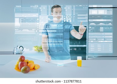 Complete control. Attentive man standing in the kitchen and frowning while touching the transparent hologram and controlling the condition of his health with a help of a special chip in his body