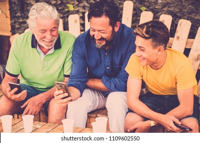 complete family caucasian people men sitting on a wodd bench looking smartphones. grandfather father and son all together enjoying the leisure outdoor time with smile and fun. technology generations