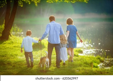 complete family consisting of a father, mother, son, daughter and their dog Beagle, walk in the evening haze at the lake