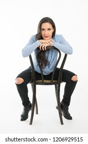 Complete shot of woman sitting on a chair backward looking camer