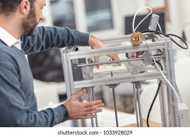 Complete work. Dark-haired bearded young engineer removing a recently printed 3D model from the printer with one hand while holding onto the body of the device with the other hand
