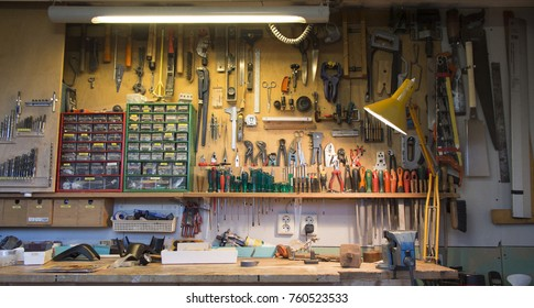 Complete workbench with a wall of tools in a workshop.