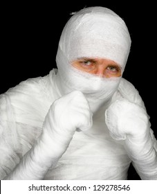 Completely bandaged man is ready to fight with clenched fists on black background