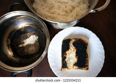 Completely burnt rice on plate next to pot standing on table in kitchen. Concept of unskilled, clumsy chef. Ruined dinner for family