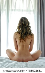 Completely naked girl with long hair sitting on a bed in the lotus position with his back to the camera in front of a large window. Woman meditating.