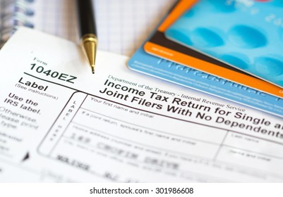 Completing 1040 tax form. Blurred credit cards on background.