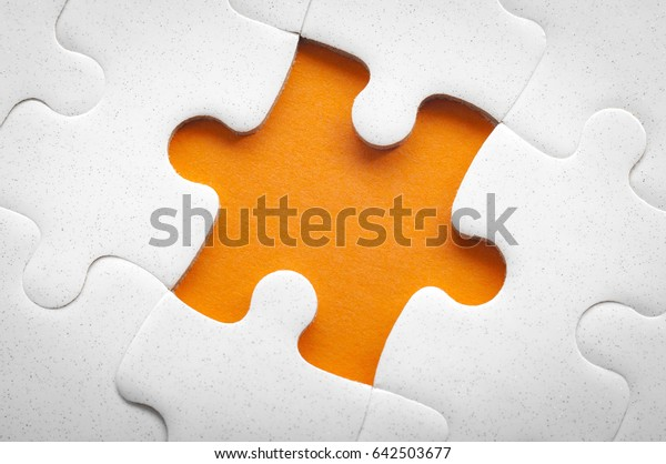 Completing final task, missing jigsaw puzzle pieces and business concept with a puzzle piece missing in the middle of the board on orange background and copy space