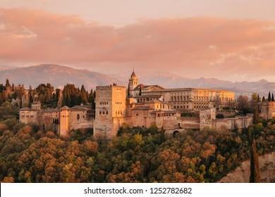 The complex of Alhambra palaces in the orange colours of the sunset with the Sierra Nevada in background