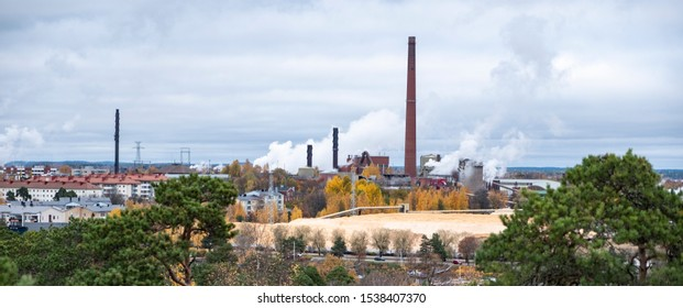 The complex of buildings of the old factory. Red brick factory chimneys with smoke. Cardboard factory in Finland, the city of Kotka
